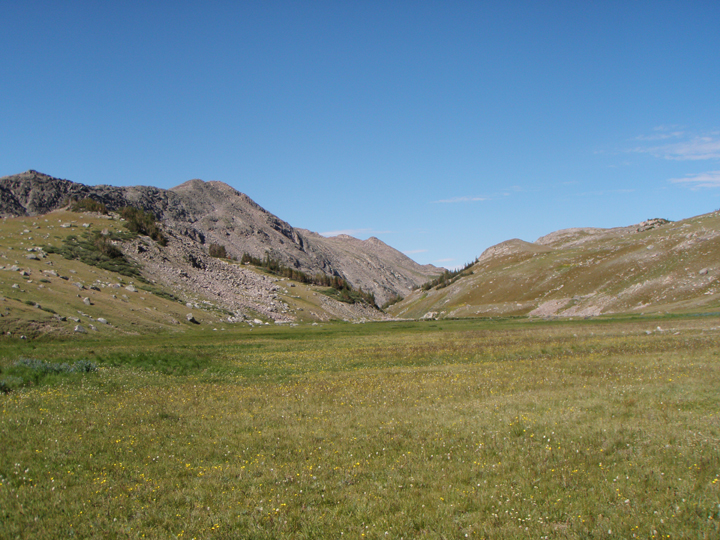 A flat grassy meadow stretches out to grassy slopes scattered with rocks.
